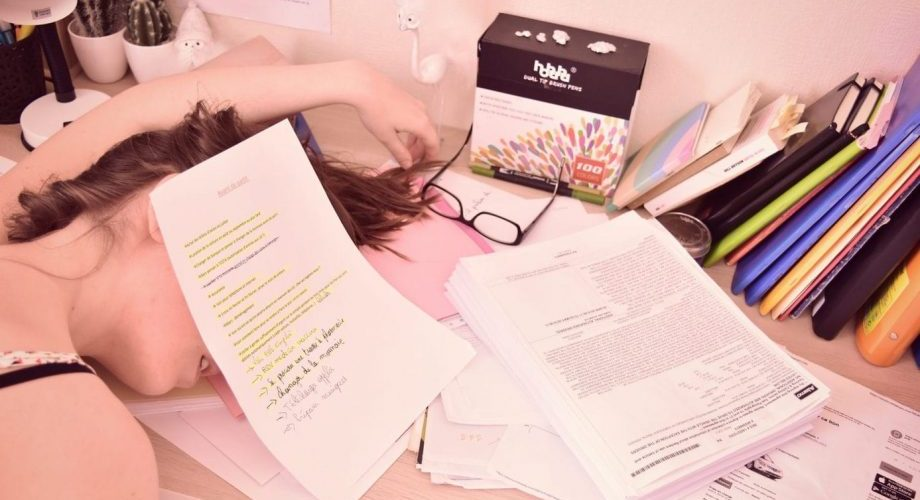 Une fille endormie sous une montagne de documents.
