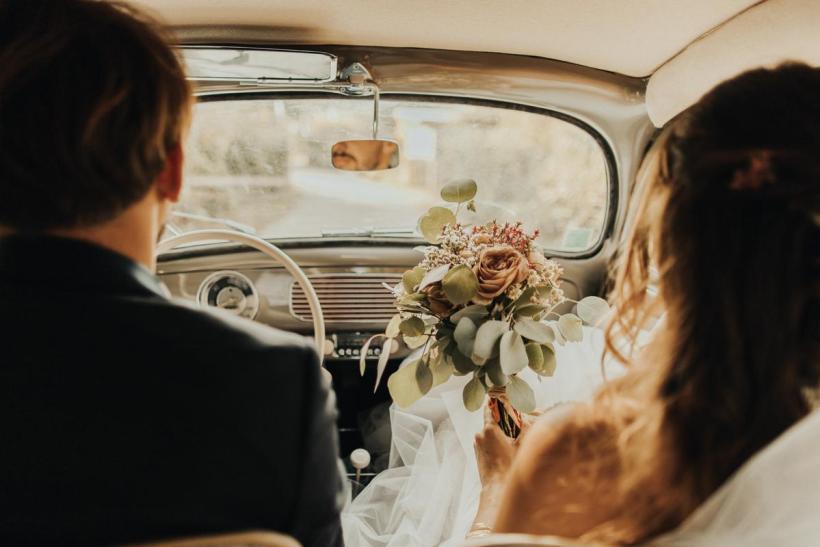 Jeunes mariés dans leur voiture de collection