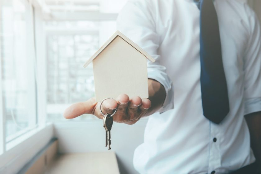 Hand agent with home in palm and key on finger. Offer of purchase house, rental of Real Estate. Giving, offering, demonstration, handing house keys.