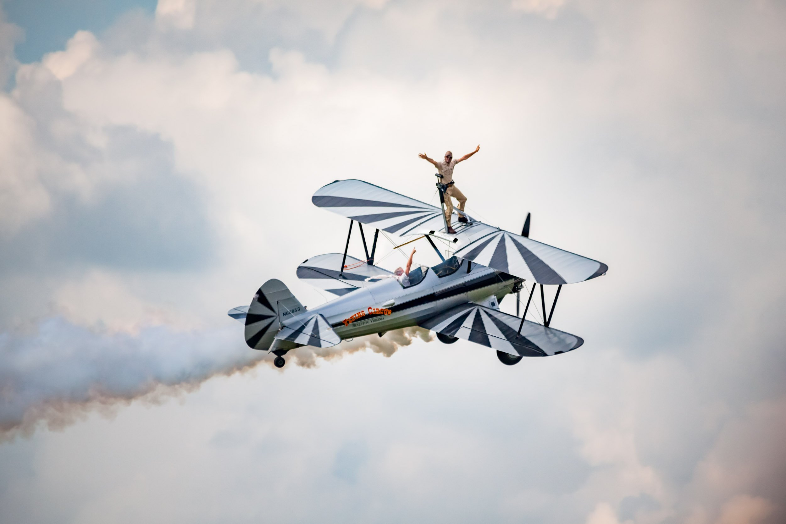 stuntman standing on a biplane wing in flight