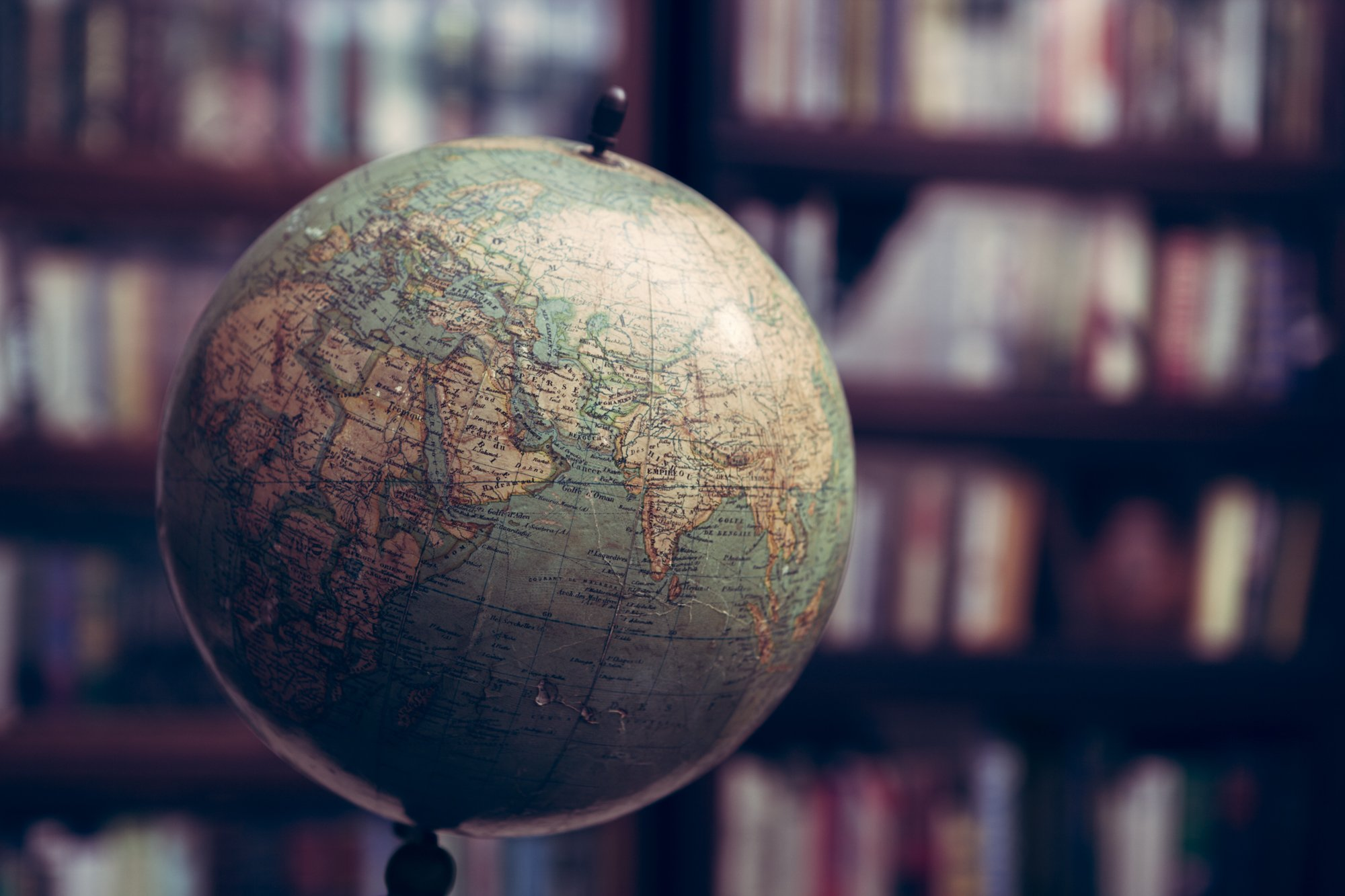 Close up of an antique globe in a library with barrister book cases from 1920s era
