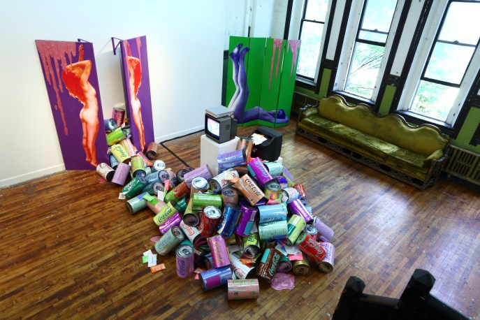 Tastier (installation shot), gallery dimensions 20' x 40' x 15'), mixed media: wood, paint, screenprints on paper, screenprints on metalized laminate, screenprints on Tyvek, cardboard, acrylic paint pours, mica powder, video, hinges, brackets, and brass chain, 2013.