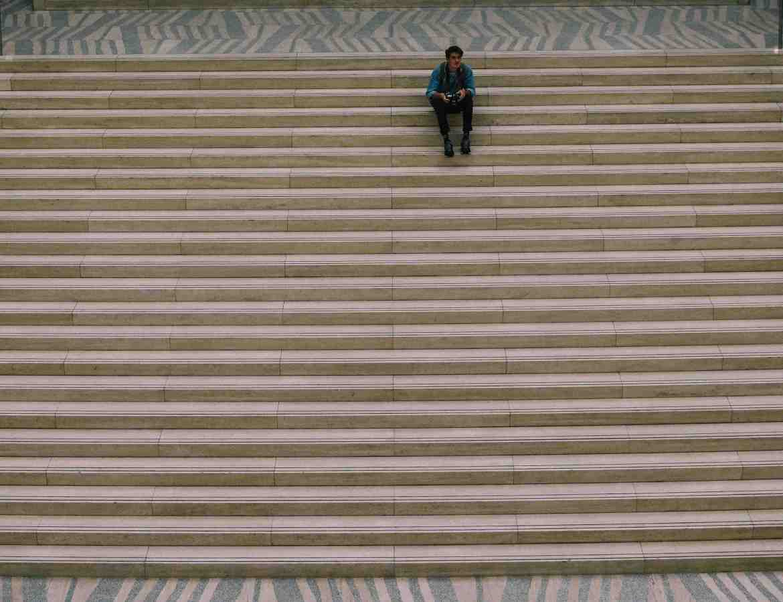 Homme en haut d'un grand escalier