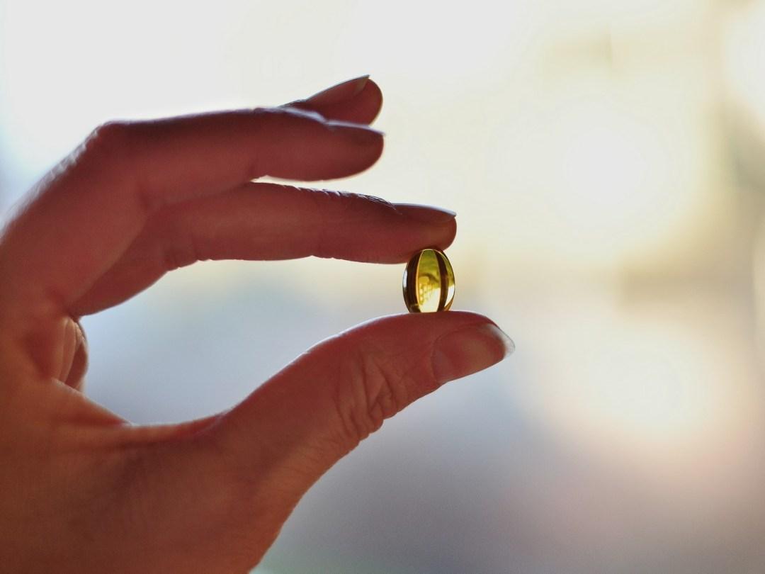 main tenant une capsule d'huile végétale