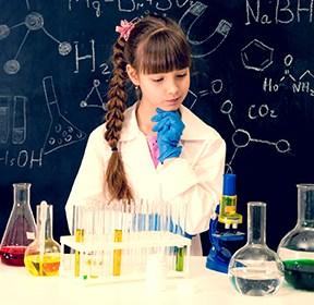 Une jeune fille réfléchit aux expérimentations qu'elle aimerait conduire dans un laboratoire de chimie