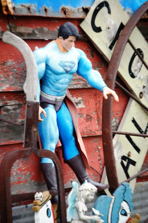 Superman is hung forever on the side of Boudreau's antiques...saving a little doll?