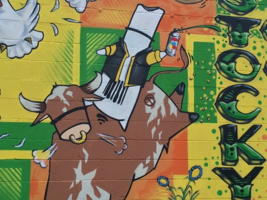 "Dronex drone riding a bull, detail of ""Stockyard Commons"" mural"