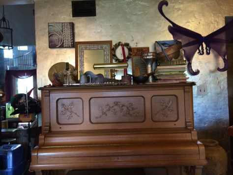 A collection of oddities on top of an old old piano