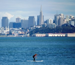 A paddle boarder in the bay with the city behind her