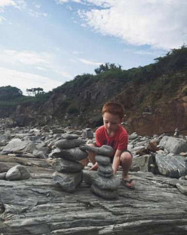 Grandson Landen makes a rock pile on the rocky shores of the Atlantic