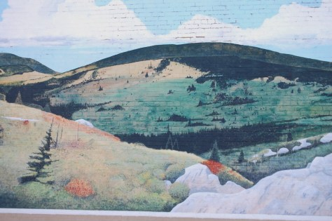 A mural of mountain scenery on the side of a building in Damascus