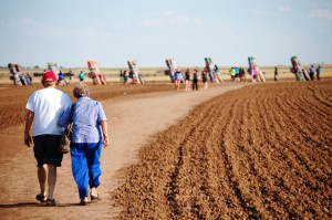 A couple walks the path to the Cadillac Ranch