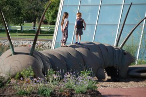 """Grandkids play on the 30 foot long """"Lopatapillar"""", a creation by artist Bob Cassilly"""
