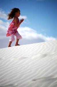 Joselyn runs on a sand dune at White Sands National Monument in NM