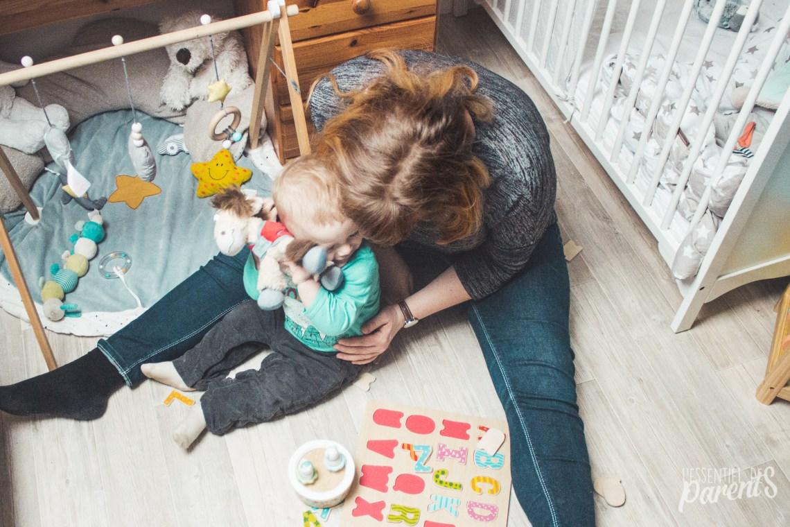 Maman enlaçant son enfant qui lui même fait un câlin à son nounours.