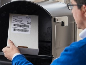 a man puts a parcel or package marked with postage in to a drop box to be returned by a carrier