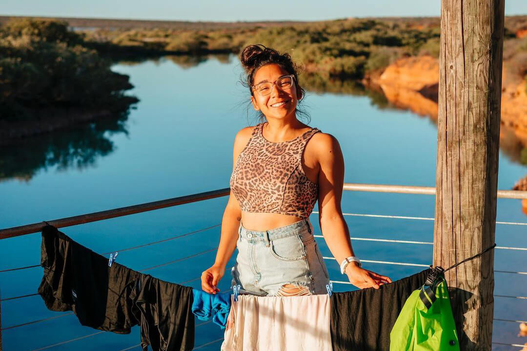 happy girl doing travel laundry outside