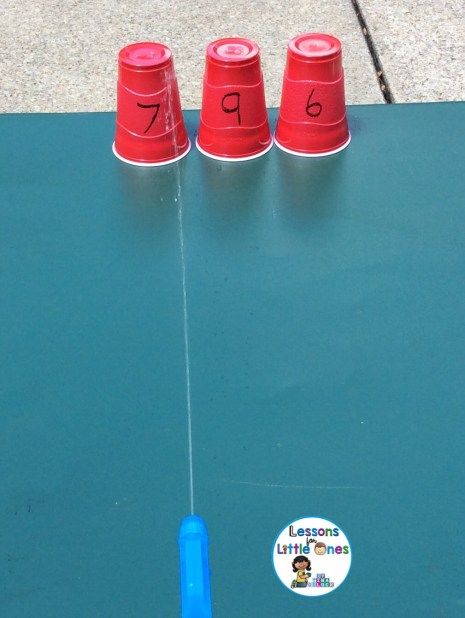 squirting water at cups with numbers learning activity