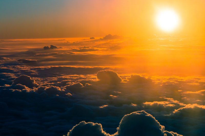 The bright sun above some fluffy clouds