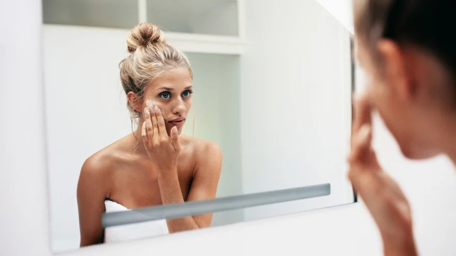 Woman cleaning face whilst looking in a mirror.