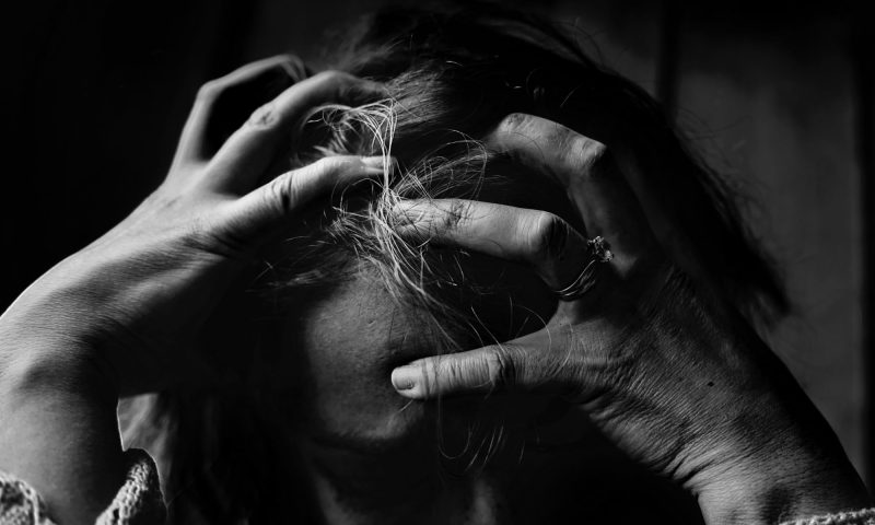 A woman holding her head due to burnout