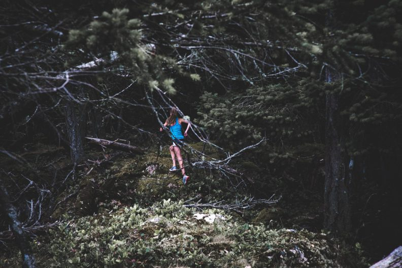 Woman running through forest.