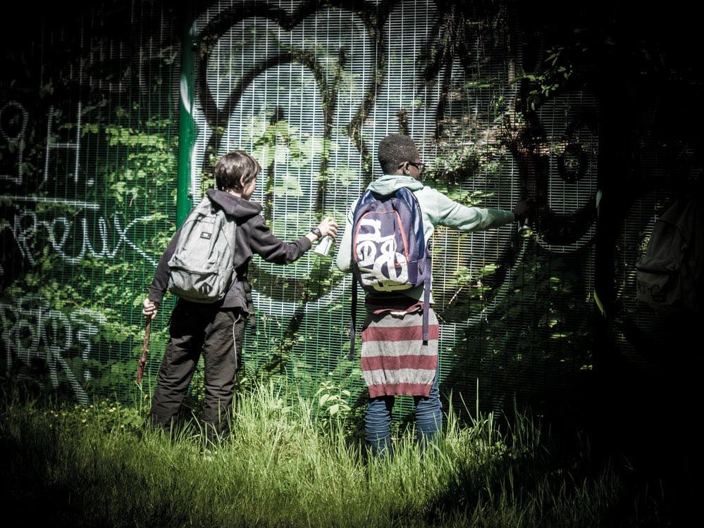enfant qui font du graffiti sur un grillage à la petite ceinture aux buttes chaumont à paris