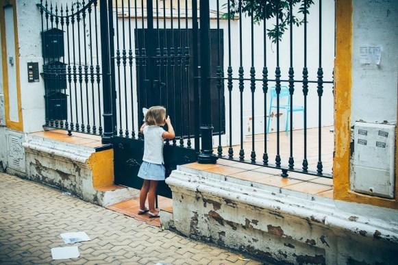 petite fille à la grille d'un portail sur la place Alameda de Hercules à seville, voyage en espagne