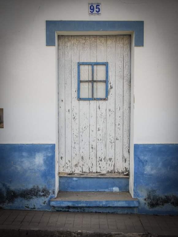 une belle porte blanche et bleu ciel au village de odeceixe au portugal voyage en algarve
