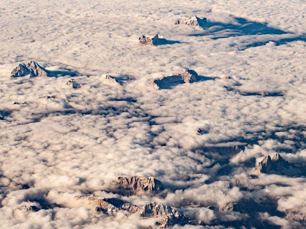 une mer de nuage vue du ciel avec des sommets des alpes qui surgissent dans le soleil