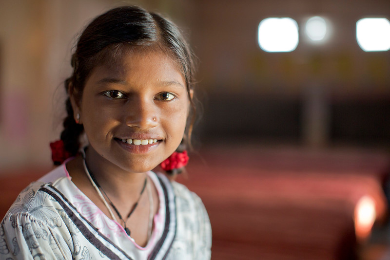 "Laxmi Pal, 12, smiles for a picture inside one of the rooms at the Udaan Girls School in Hardoi, India. She, along with 24 of her classmates, created pieces of art for CARE's ""International Day of the Girl"" art exhibition in Atlanta, GA. This exhibit also marked CARE's 20th anniversary in Atlanta. Photo by Josh Estey."