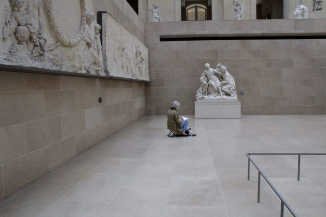 A person sketching in the Louvre Museum in Paris France
