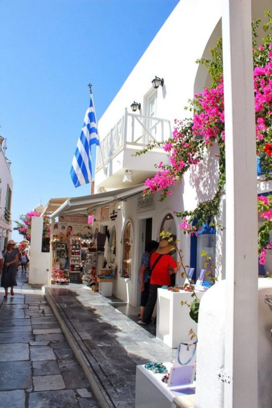 A beautiful storefront in Oia Santorini with a Greek flag out front