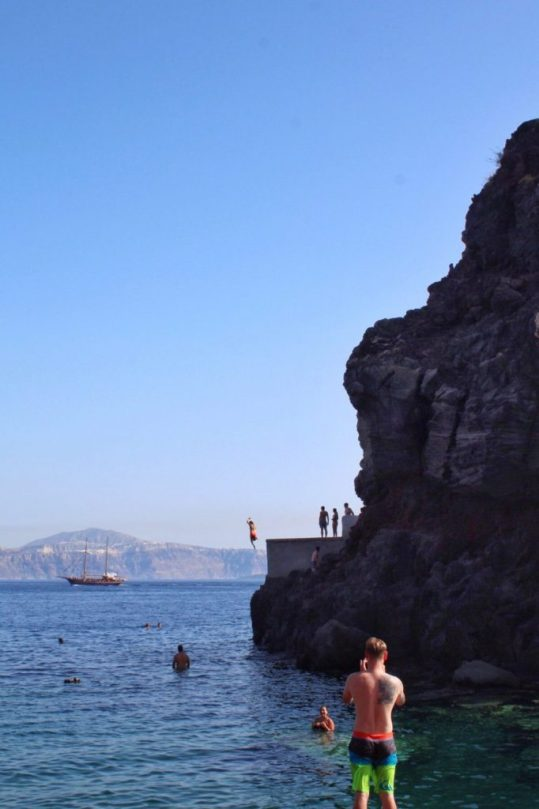 A guy jumping from the swim platform at Amoudi Bay Santorini