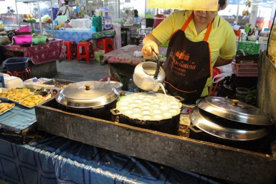 A lady making fried coconut milk balls in the Chiang Mai Market