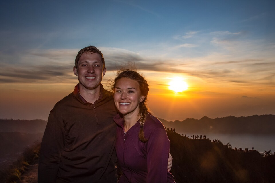 Lauryn and Eric on top of Mount Batur with the sunrise in the background