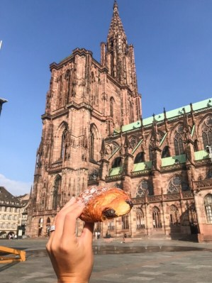 Eating a pastry in front of the cathedral in Strasbourg, France