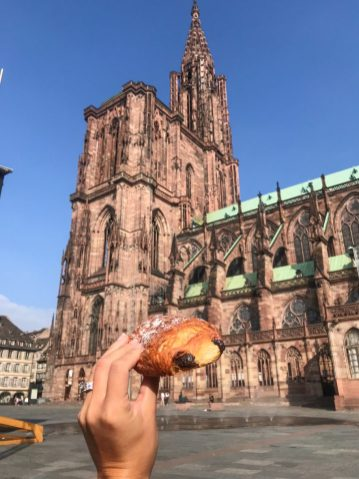 Eating a pastry in front of the cathedral notre dame in strasbourg france