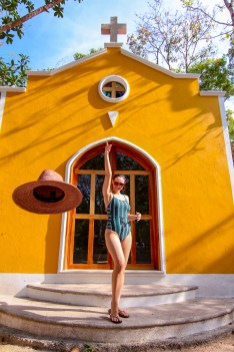 girl throwing hat in the air in front of yellow building