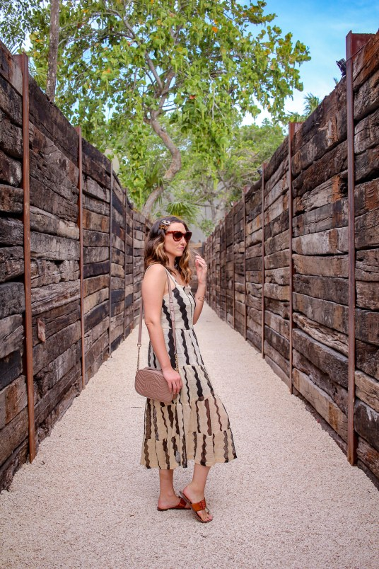 girl with striped dress stading in the middle of two wooden walls