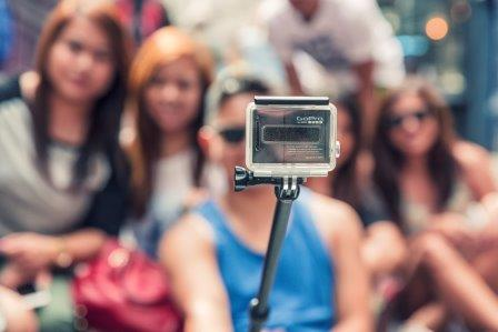 Man taking film with selfie stick