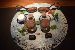"Various homemade chocolates with edible flowers. At the bottom is written, ""Happy birthday, Midori"" in Spanish."