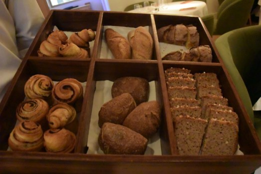 The very elegant bread basket featuring olive bread, corn bread, and other selections.