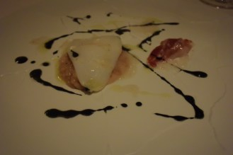 Grilled squid over squid rice, lemon zest, bone marrow, and pancetta emulsion.