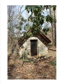 a small stone building in the woods
