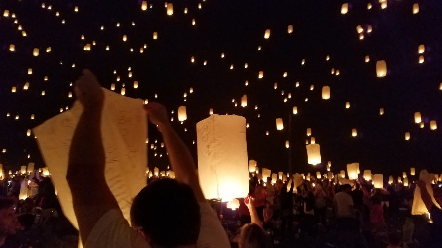 Lots of people letting go lanterns into the night sky