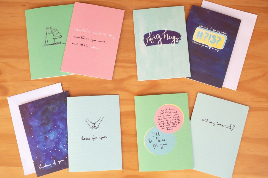 A colourful collection of bereavement cards laid out on a table