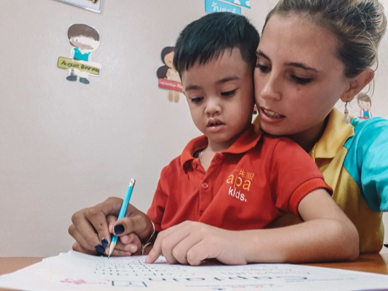 Teacher Chane helping one of the students write in Thailand.