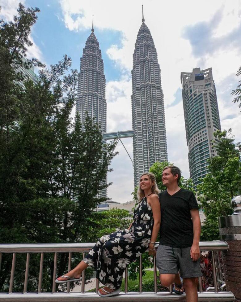 a couple enjoying the beautiful park behind the Petronas twin towers