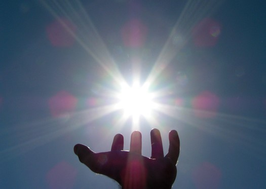 Hand reaching for the Sun against a dark blue sky. The Sun is surrounded by ray and there are purple spots of light in the sky